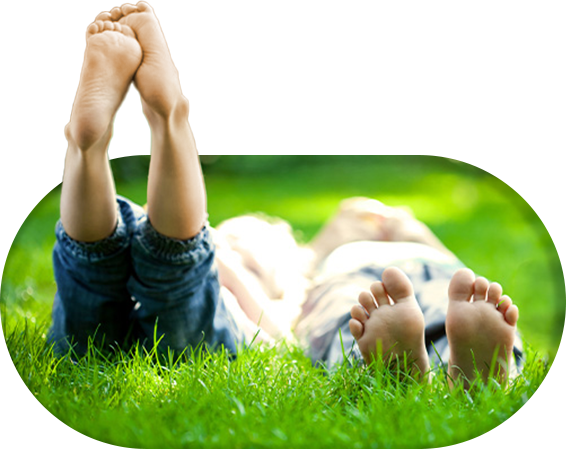 Kids lying on grass with bare feet up in the air.